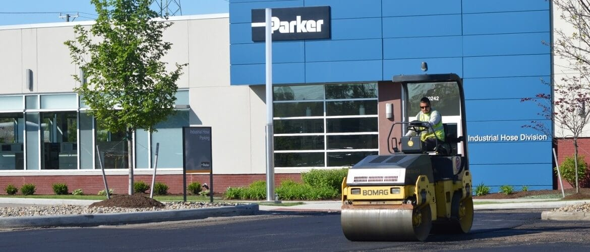An asphlat compactor smooths the surface of a parking lot paving job in front of Parker Hannafin's corporate office.